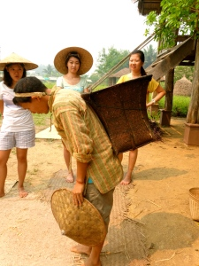 Lee carrying a basket of rice the traditional way with the strap over his head.