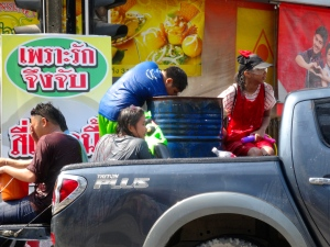 Pick-up truck carrying a bed of people and their barrel of water.