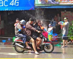 Motorcycle water battle.  Notice that the third person on the back of that motorcycle has a water gun.